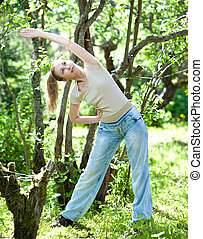 The young slender woman does sporting training in park