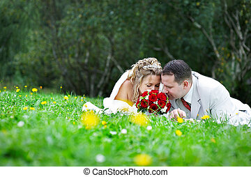Bride and groom are on the grass and sniffing bouquet -...