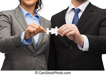 businessman and businesswoman with puzzle pieces - business...