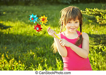 girl with pinwheel - cheerful little girl playing with...