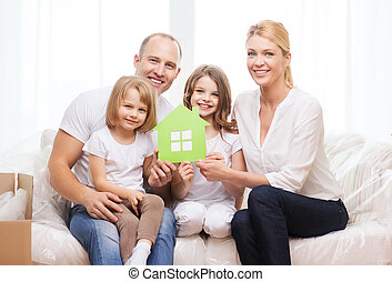 smiling parents and two little girls at new home - family,...