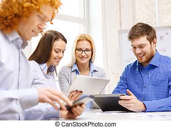 smiling team with table pc and papers working - business,...