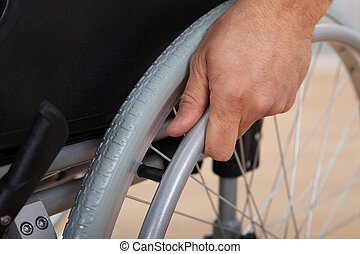 Handicapped Man's Hand Pushing Wheel Of Wheelchair - Closeup...