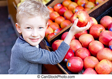 kid shopping - adorable little boy choosing fruits at the...