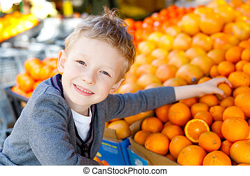 kid shopping - smiling little boy choosing fruits at the...