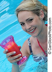 Beautiful young woman in a pool with a cocktail - Beautiful...