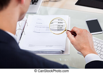 Auditor Examining Invoice With Magnifier - Cropped image of...