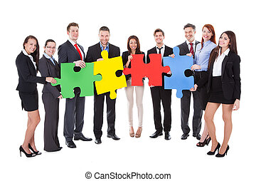 Group of businesspeople holding puzzle pieces - Group of...