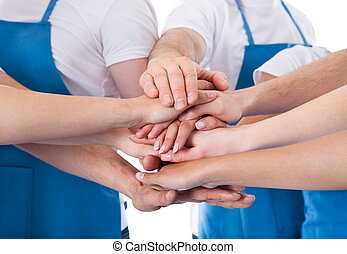 Group of cleaners stacking hands - Low angle view of...