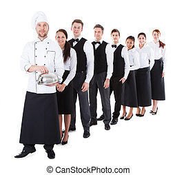 Large group of waiters and waitresses standing in row....