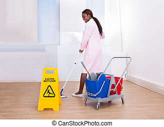 Female Housekeeper Cleaning Floor In Hotel - Full length of...