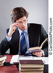 Handsome lawyer in elegant suit  with book in hand