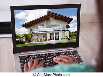 African American woman selecting new house on laptop at home...