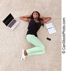 Young African American woman relaxing on rug at home