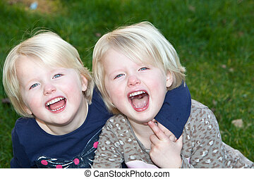 Beautiful little blond identical twins girls posing together...