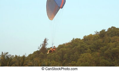Paragliding over the mountains is landing in tropics against...