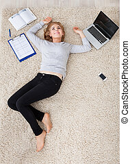 Young Woman Lying On Carpet - High Angle View Of Young...