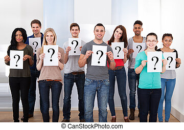College Students Holding Question Mark Signs - Group...