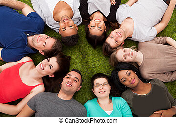 Portrait Of Confident College Students Lying On Grass - High...