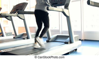 People at the gym exercising Run on a machine Out of focus