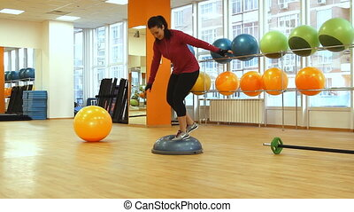 Young woman doing exercise with bosu ball