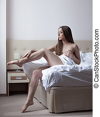 Attractive young woman posing sitting on hotel bed