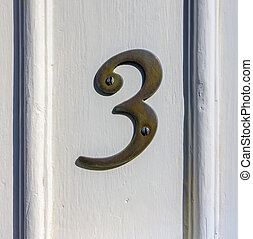 Number 3 - Bronze house number three attached to a wooden...