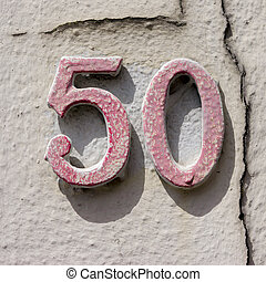 Number 50 - Red house number fifty next to a crack in the...