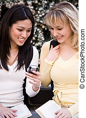 College students - A shot of two college students texting...