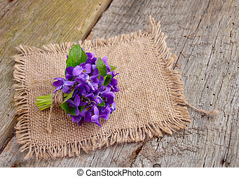 Small bouquet with meadow violets on board