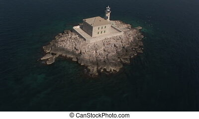 Aerial view of a small island with a lighthouse on the...