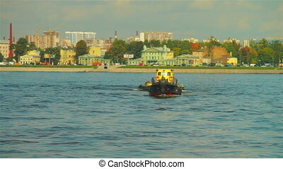 Small load ship with boat on hook passing through Neva river...