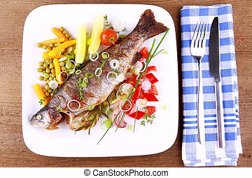 Grilled trout with quite different vegetables with cutlery,...