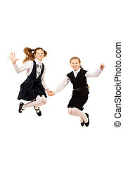 laughing - Two ten years girls in a uniform jumping for joy...