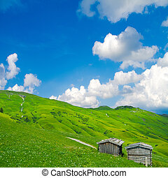 rural alpine landscape with wooden huts an beautiful sky