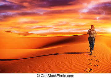 Woman traveling in the desert - Active woman trekking along...