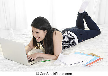 chinese student or business woman lying on bed computer...