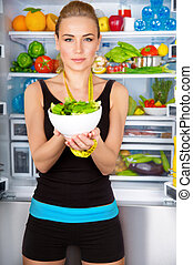 Healthy woman with fresh salad standing near open fridge...
