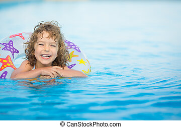 Child in swimming pool - Happy child playing in swimming...