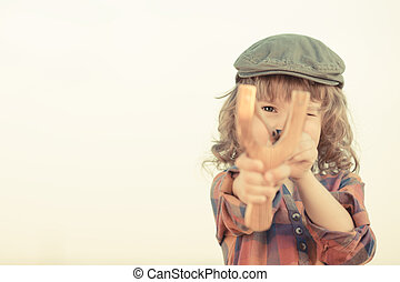 Child holding slingshot in hands against summer sky...