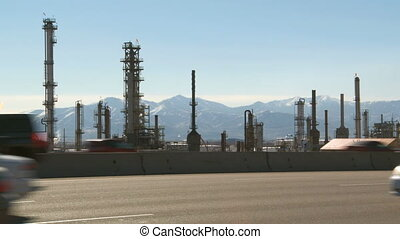 Highway traffic and oil refinery - Busy highway traffic with...