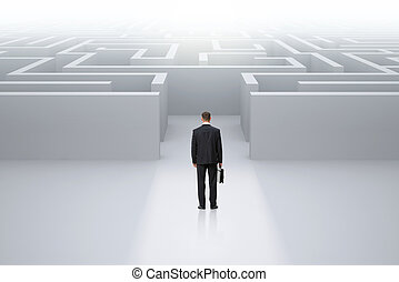 Businessman with case standing in front of maze