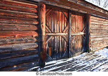 wooden farm barn house with closed door in winter