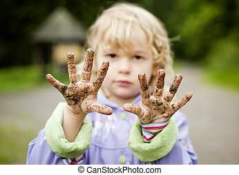 Cute girl - Little girl with her muddy hands in green park