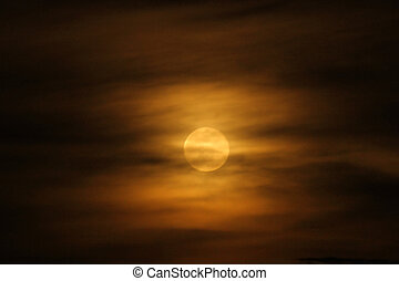 Full Moon in Orange Clouds - A full moon rises throgh the...