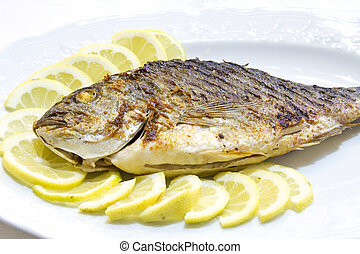 Fish - Grilled sea bream with lemon slices on white plat