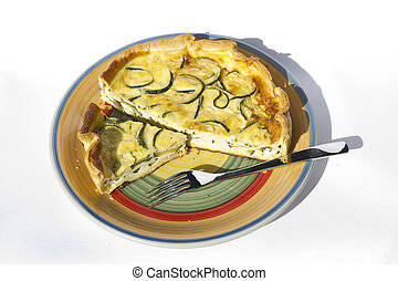 Quiche lorraine with eggs and zucchinis on a white...