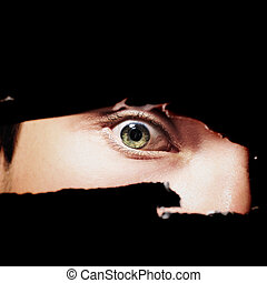 Scary eye of a man spying through a hole in the wall closeup