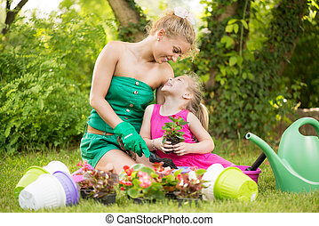 Beautiful mother and daughter planting flowers