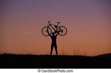 Mountain biker - Silhouette of mountain biker holding his...